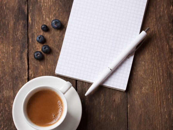 Notebook and coffee with copy space on a wooden background. selective focus