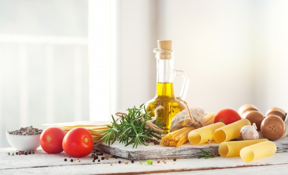 Healthy ingredients on a kitchen table - spaghetti, olive oil, t